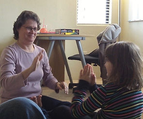 Kim and Gracie, a school-aged girl, are involved in a HANDLE clapping pattern