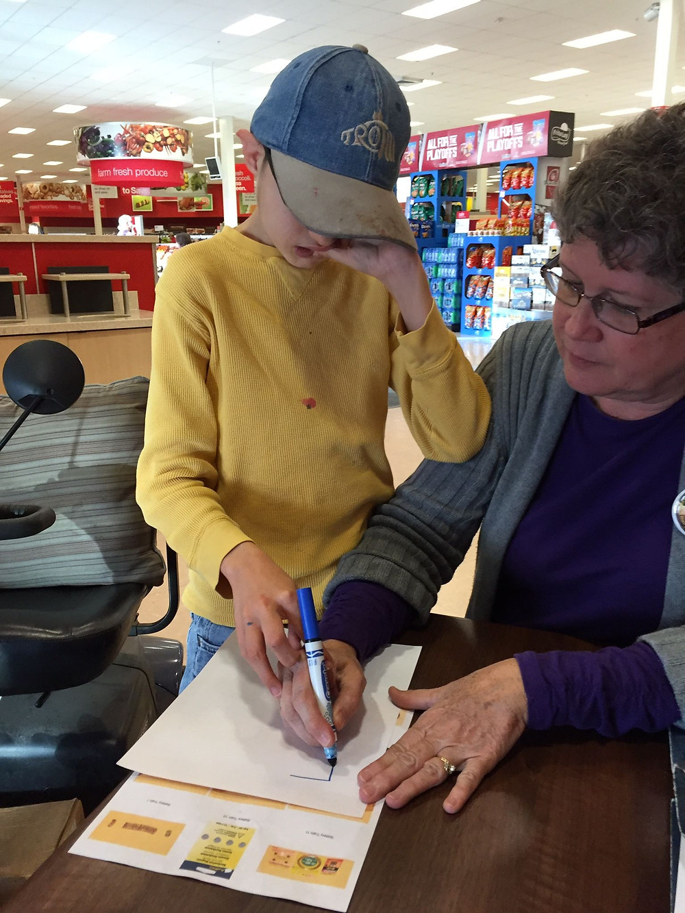 I am sitting at a table in Target with Dylan standing beside me, his right hand on mine, as I begin to draw a square, which will become his symbol for batteries.