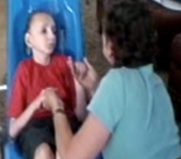Blurry image highlighting the connection between Kim and Kenzie, a school aged boy who became deafblind as a preschooler, his hands are in hers, as he lifts his head to look towards her