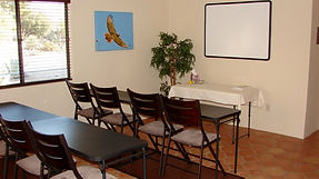Tables and chairs face a presentation board with a large photo of a soaring redtail hawk on the wall