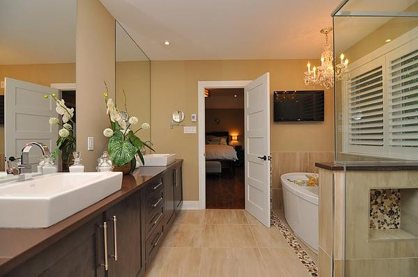 SCM Design Group sleek master bath with double vanity and chandelier over tub