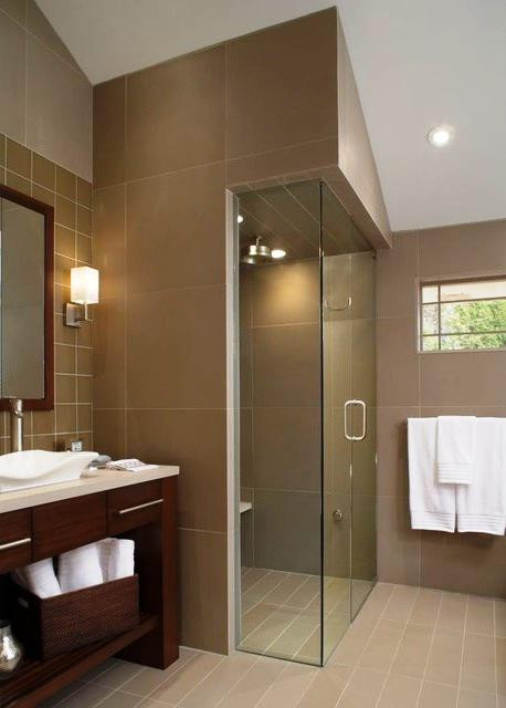 SCM Design Group glass shower doors with tiled wall