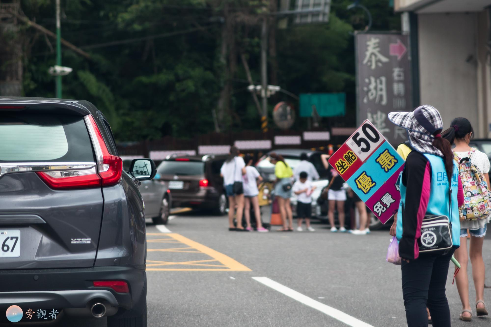 在日月潭環湖公路邊舉著船票銷售廣告牌的人。南投魚池