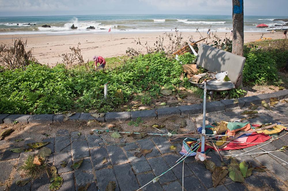 墾丁國家公園的觀光景點-船帆石沙攤旁的人行道上散落著損壞的洋傘,一旁的草叢堆置著廢棄物。屏東恆春。2017/8/3 09:02。