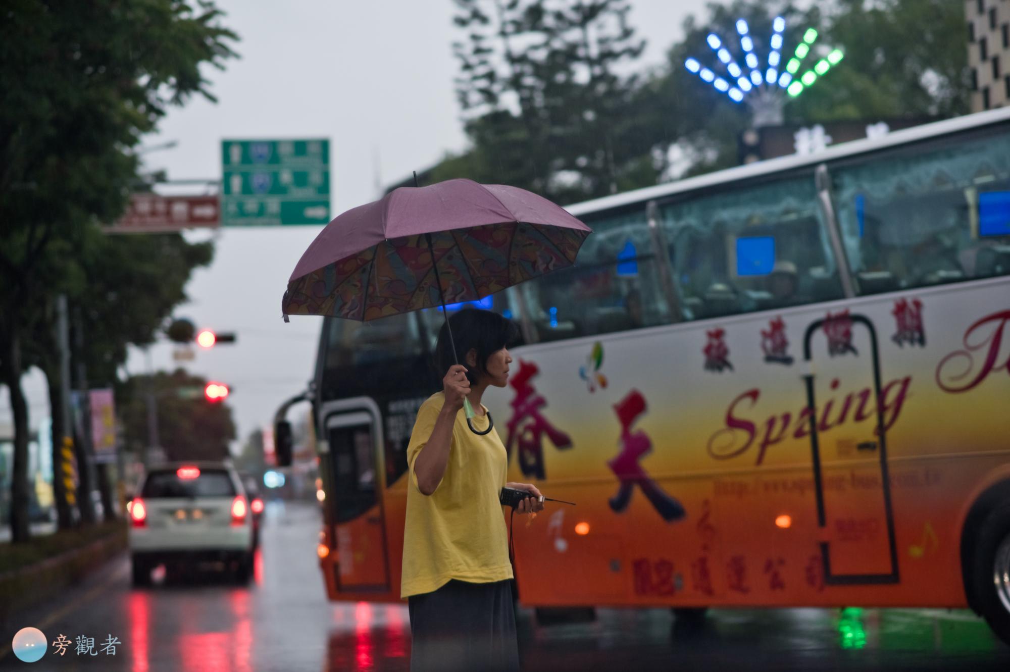 一位女士站在道路上阻止來往車輛,以協助遊覽車倒車停入餐廳的停車區。南投埔里西門