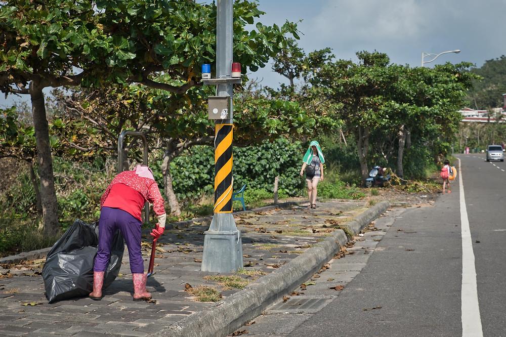 一個人在墾丁國家公園的觀光景點-船帆石沙攤旁的人行道上撿垃圾。屏東恆春。2017/8/3 09:04。