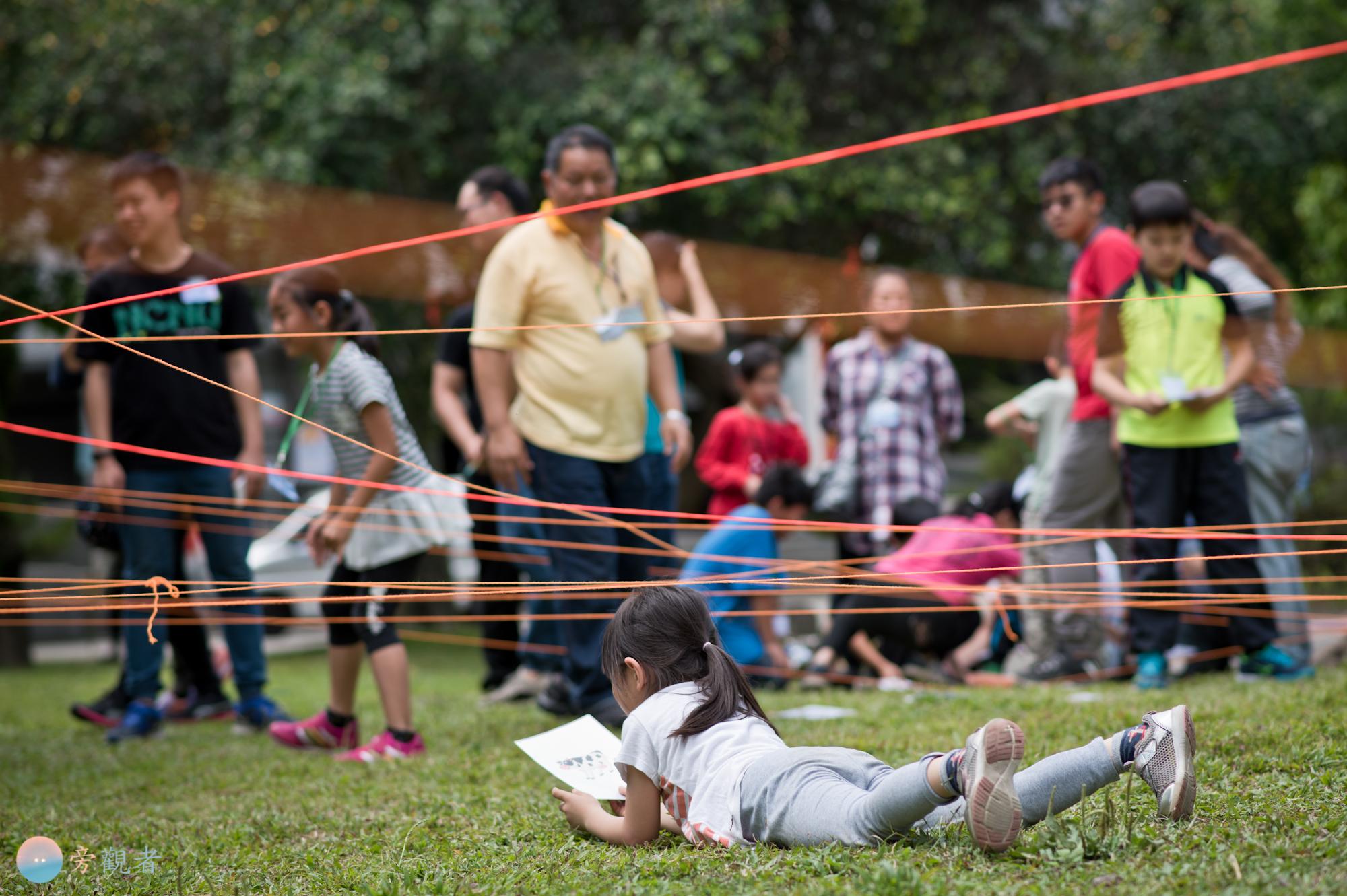 參與親子闖關活動的小孩在草地上爬行完成任務。南投埔里。2018/4/14