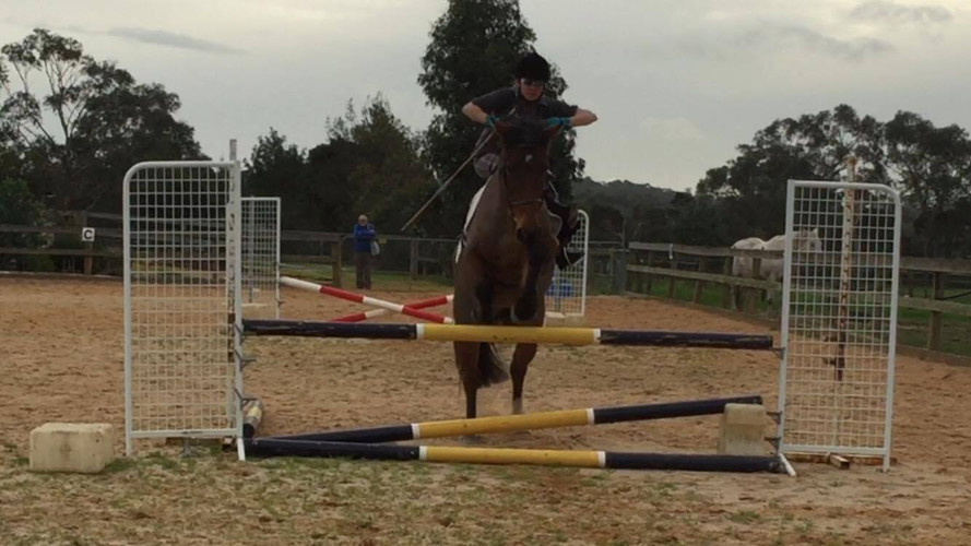 Student Kate in a side saddle jumping lesson.