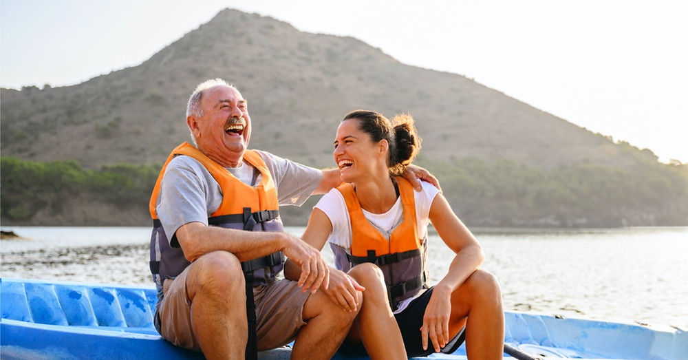 Elderly man with granddaughter taking a break from kayaking. She will treasure this memory, and it wouldn't have been possible had he not been healthy enough to enjoy an excursion such as this one.