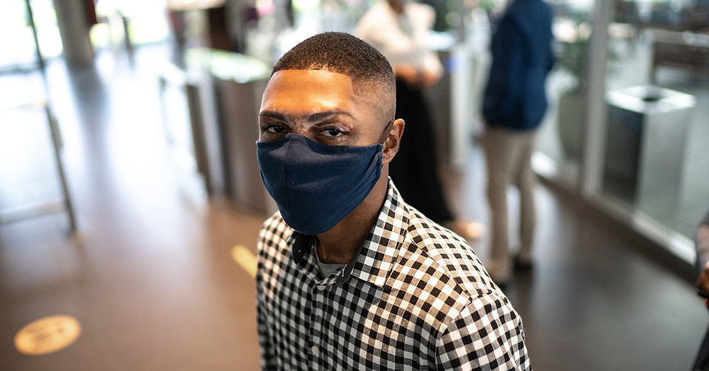 Man in office lobby waiting and wearing face mask. He had been a U of I employee, but because of current circumstances, he has changed career goals.