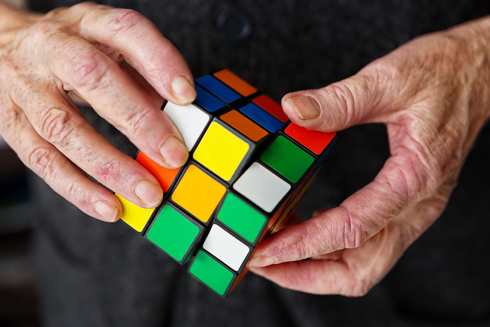 An elderly person's hands manipulate a Rubik's Cube, hopefully keeping his or her mind active. This image symbolizes the frustrations, problems and puzzles facing seniors, such as retirement planning. The cube was invented in 1974 by Erno Rubik, a Hungarian. More than 350 million have been sold.