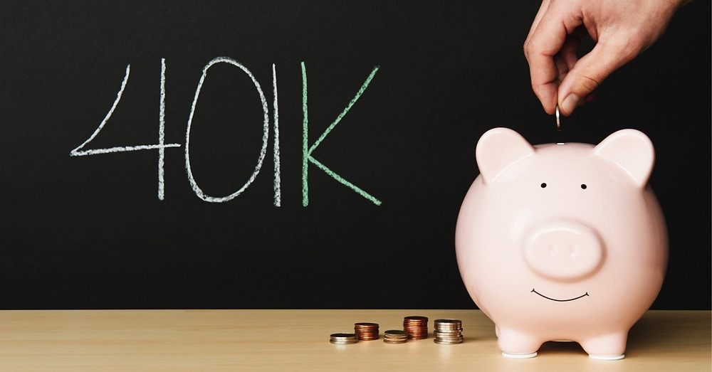 A piggy bank sits on a wooden table with stacks of coins beside it. Your hand emerges to put a coin into the piggy bank. Investing in your retirement savings through a 401K is a top priority for you.