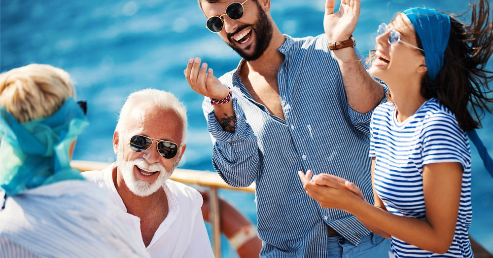 Man in his 60's enjoying carefree laughs on yacht with grown up grandchildren.