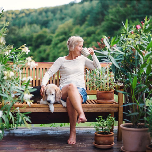 senior-woman-retired-from-esop-with-a-dog-and-coffee-sitting-outdoors.jpg