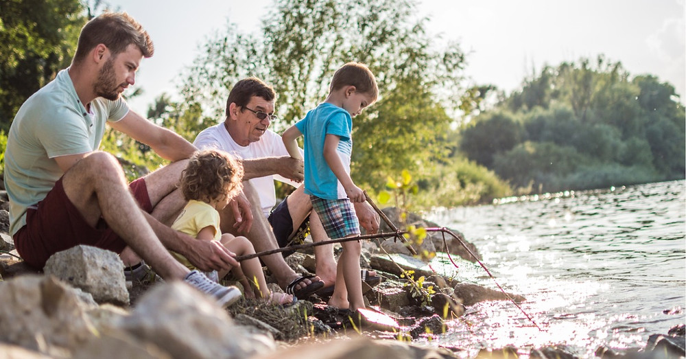 grandparent fishing with son and grandsons enjoying retirement