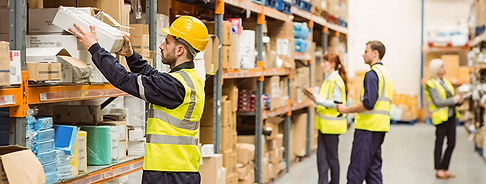 Worker in Warehouse Putting Supplies on Shelf