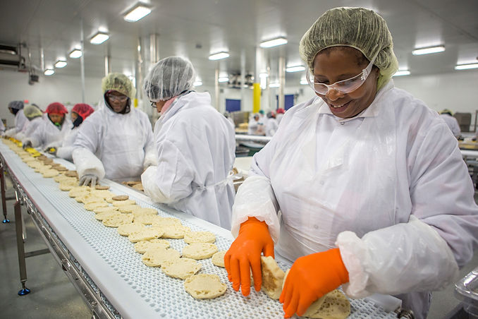 Food Production Worker Assembling Sandwiches in Factory