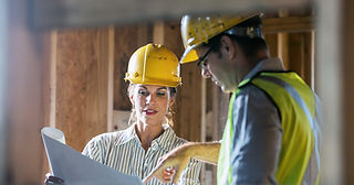 Female Project Manager discusses blueprints with Construction worker