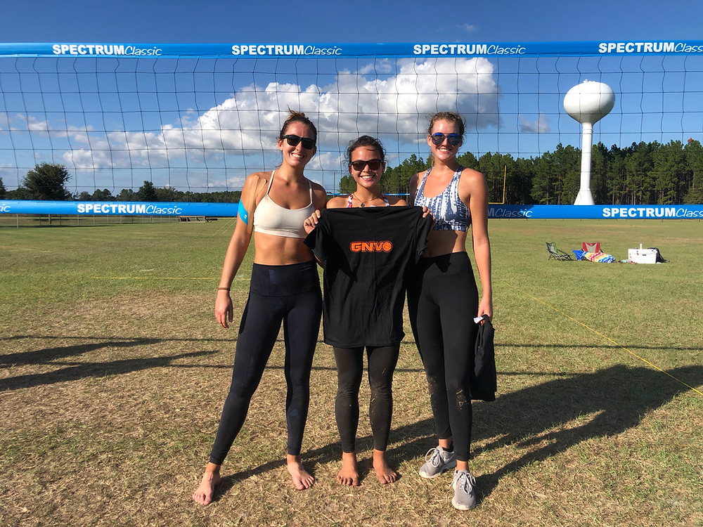 3 women standing in front of grass volleyball court and net