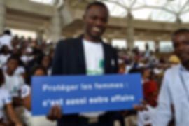 Man holding sign at Break the Silence launch, IRC, Côte d'Ivoire
