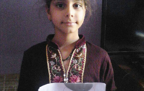 Aarna, 8-year-old Indian girl stands with drawing