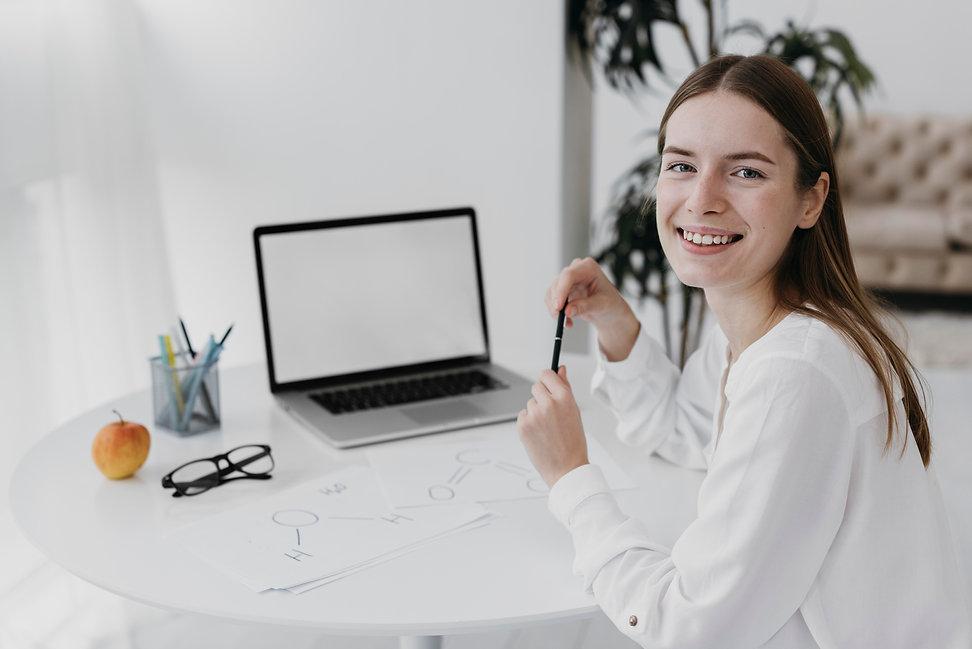 smiley-teacher-in-front-of-her-laptop.jp