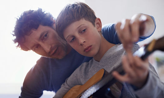 A freelance tutor on Uedify teaching a youth student how to play guitar. Become a freelance tutor today.