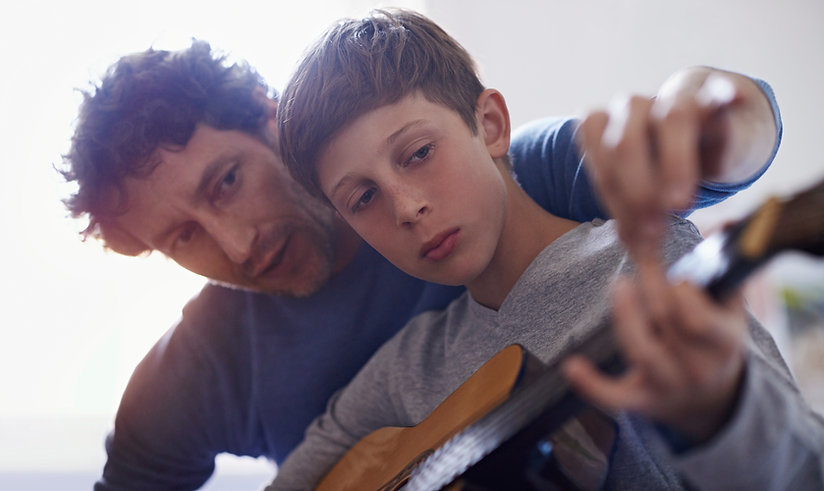 beginner guitar student learning the instrument with the teacher