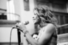 Nicole Henry singing live on stage at a jazz club. We see her holding the microphone closer to her face. Main header image of her Artist Page on the ANG Productions website.