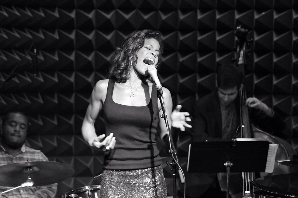 Nicole Henry singing at jazz club. The image depicts Nicole singing into her microphone passionately with her eyes closed. A true diva shot.
