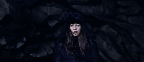 """Angie Capo in costume as the Raven and on the set of """"Wings of the Pariah"""" directed by photographer Cristina Isabel Rivera. Angie is wearing black lipstick and makeup and is standing in the center of a black cave on Diamond Beach, Iceland."""