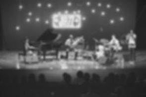 Jazz band performing live on stage. Behind them is a neon light sign that says JAZZ. In the center of the image is a bass player, with the drummer on his left and the pianist on his right.