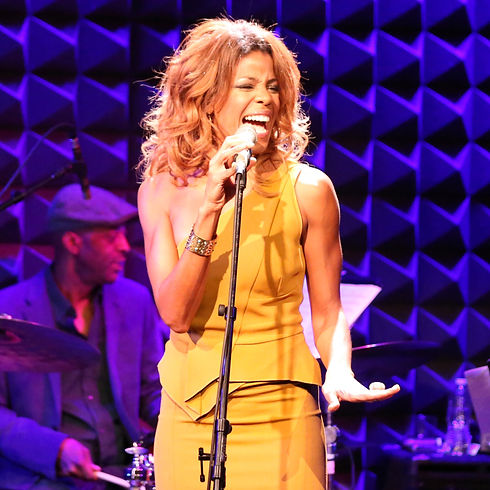 Nicole Henry live shot of one of her performances. Nicole is captured singing while holding her stage microphone and wearing an orange/yellow dress.