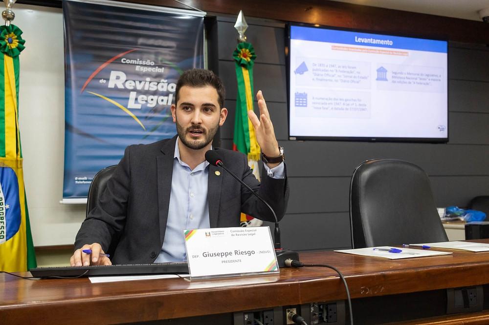 deputado giuseppe riesgo sentado em frente a apresentação de slides de resultados da comissão especial de revisão legal