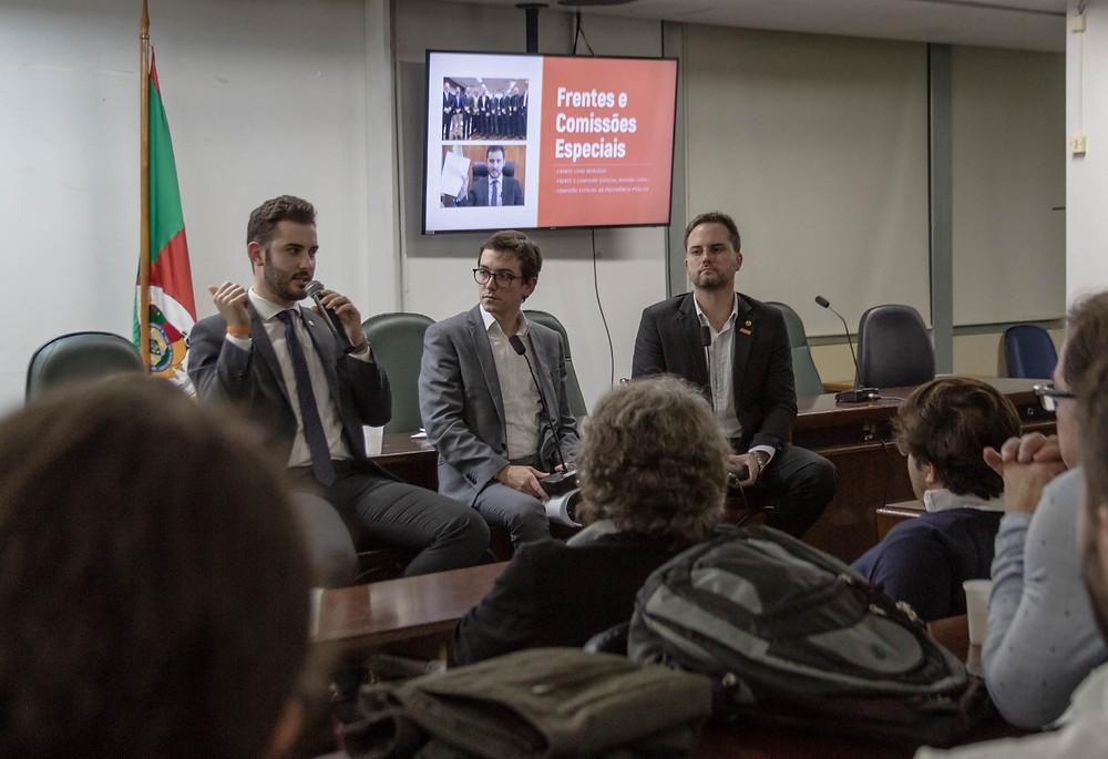 Giuseppe Riesgo, Frederico Cosentido e Fábio Ostermann sentados em frente à apresentação em slides dos 100 primeiros dias de mandato