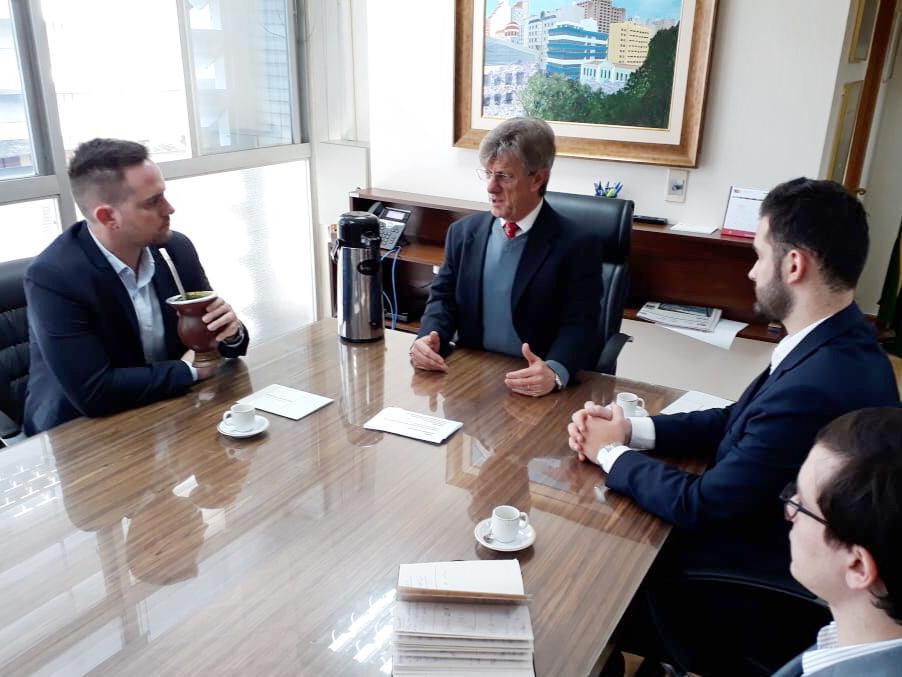 Fabio Ostermann tomando chimarrão sentado mesa de reunião com presidente do tce e giuseppe riesgo