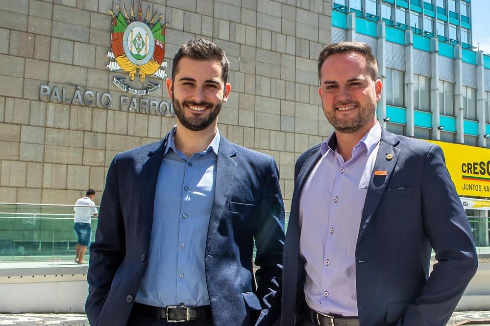 Giuseppe Riesgo e Fábio Ostermann lado a lado sorrindo em frente ao prédio da Assembleia Legislativa do RS