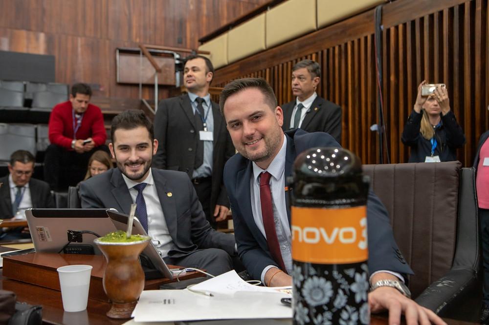 giuseppe riesgo e fabio ostermann sorrindo sentados no plenário com chimarrão após aprovação de privatização