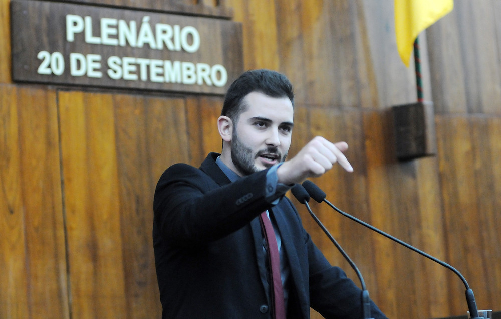 giuseppe riesgo falando incisivo na tribuna com microfone à frente e a placa do plenário 20 de setembro ao fundo