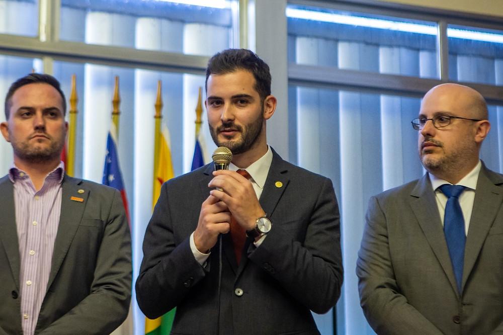 deputado giuseppe riesgo ao lado de fabio ostermann e rodrigo lorenzoni em pé com microfone na mão durante solenidade de abertura da frente parlamentar