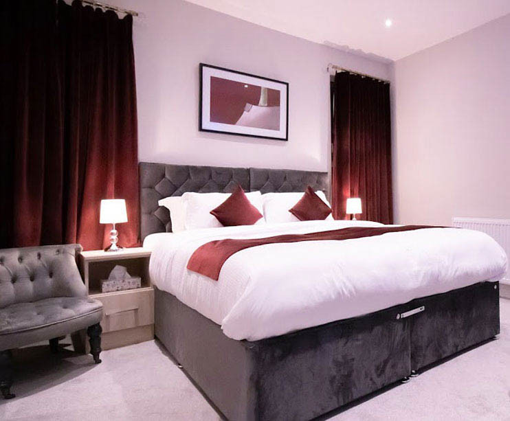 A king size bed on a cozy room, soft pillows and clean linens with lampshades on both sides