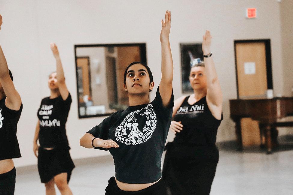 a female polynesian dancer mid movement as she dances