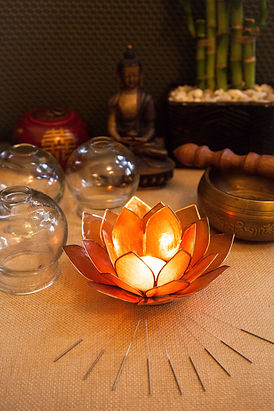Lotus candle and needles on table with buddha