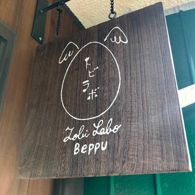 「Tobilabo Beppu トビラボ ベップ」  トビイ ルツのプライベートギャラリー。実験と創造性を象徴する卵をモチーフにしたブランドロゴ。同じく卵をモチーフとするブランドロゴをもつ「湯治宿ひろみや」に隣接するテナントのひとつ。