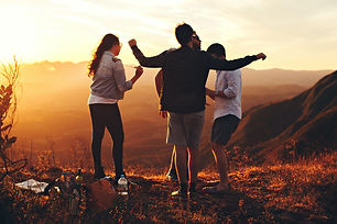 four-person-standing-at-top-of-grassy-mo