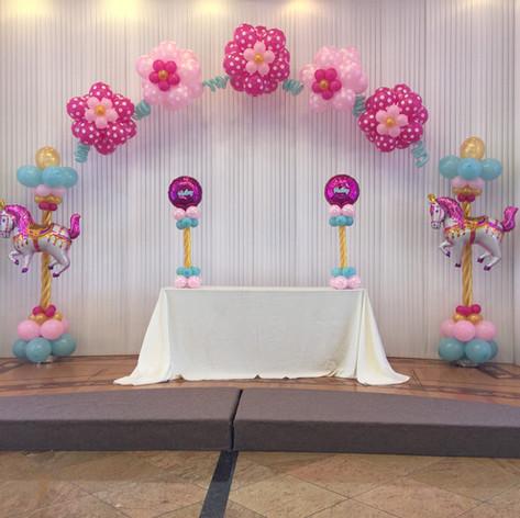Carnival Balloon columns with flower balloon arch