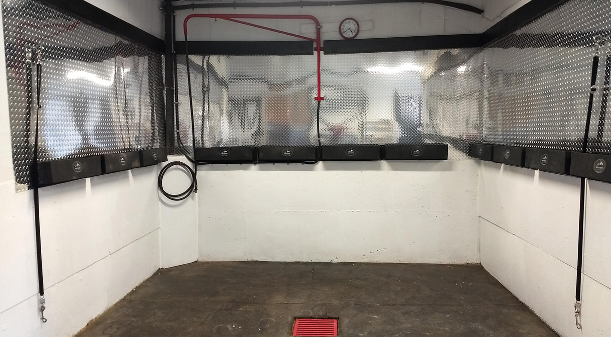 Glamorous washing area with hot/cold water, rubber mats and totes along the walls for all those horse supplies.