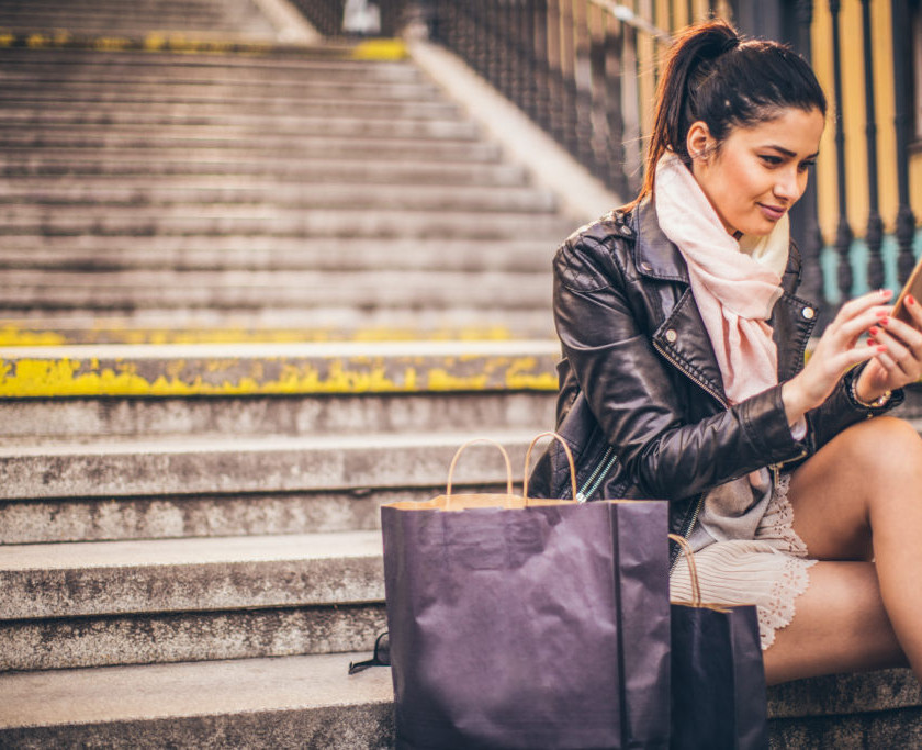 Photo of beautiful brunette using smartphone outdoors and sitting at the stairs. Shopping bags next to her.