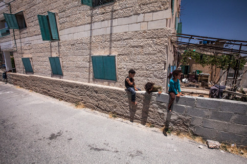 Kids sitting on a wall West Bank