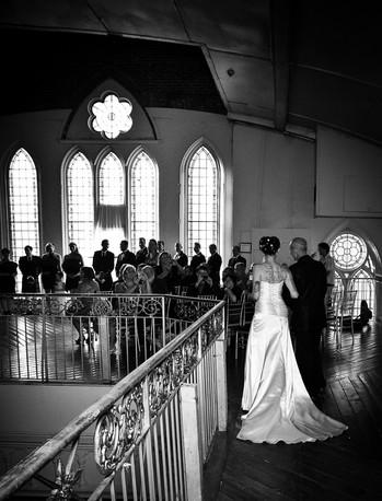 Black and White Photo of Bride with Wedding Dress Train Walking down Aisle at Berkley Church in Toronto Ontario